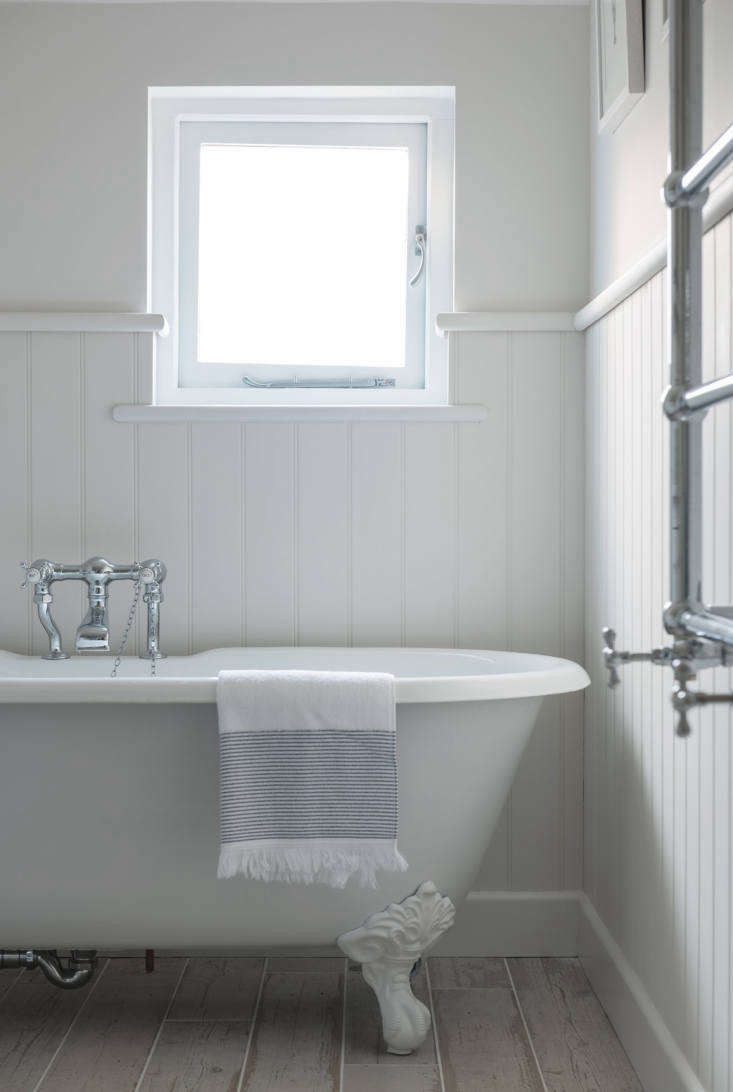 A claw-footed tub and wall-hung heated towel rack.