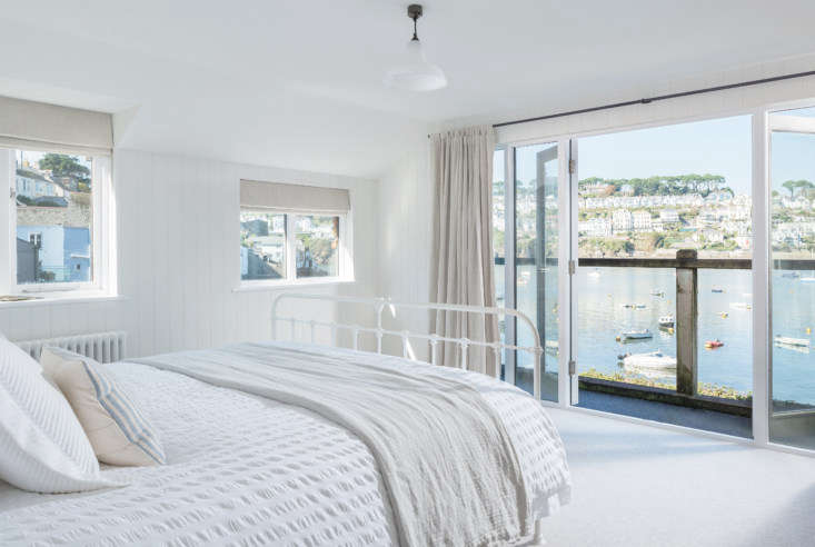 A master bedroom with a view. The balcony has bifold double doors. The cast-iron bed is the Maude from the Cornish Bed Company.