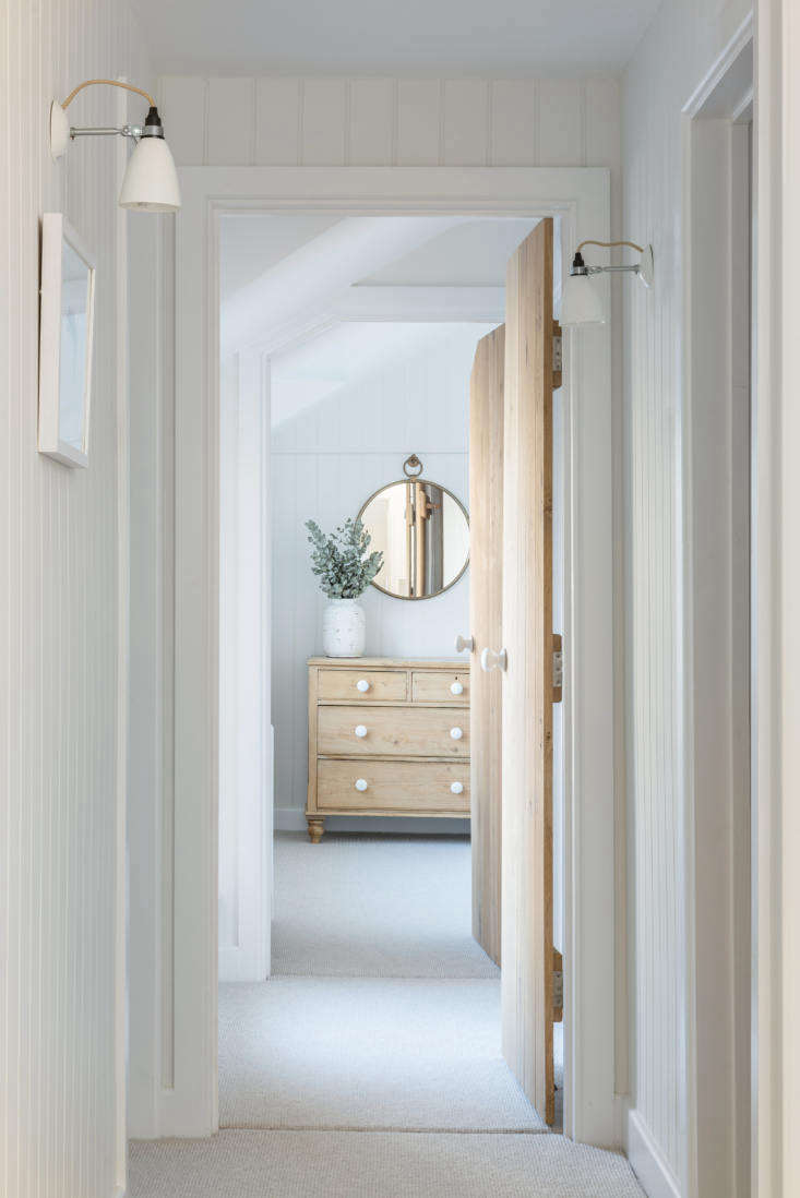 Original BTC porcelain Hector Wall Lights in the paneled bedroom hall. Note the paneled wood doors. The antique pine dresser has been updated with porcelain knobs similar to the ones used in the kitchen and on the doors.