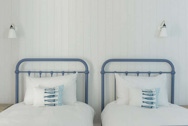 Twin cast-iron beds in cornflower blue in the guest room. There are five bedrooms total.