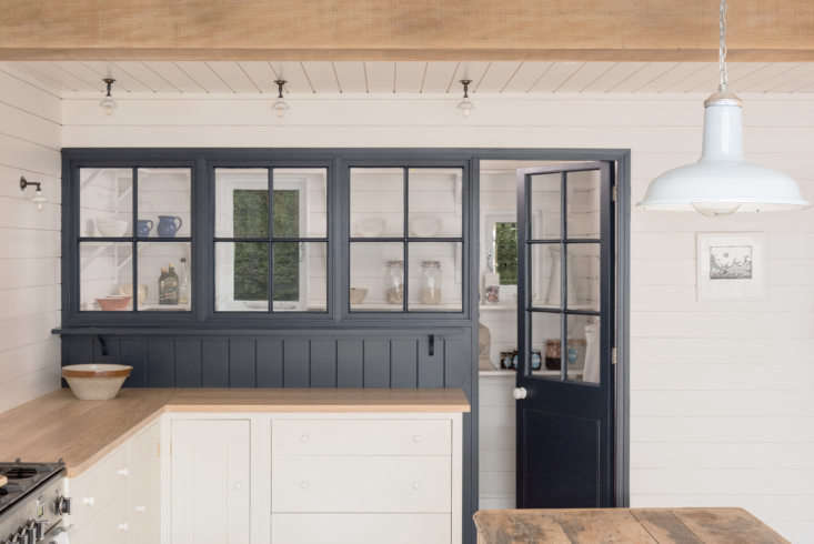 The designers introduced interiors windows throughout, including this glazed pantry painted Basalt, a rich blue-black from Little Greene. There&#8