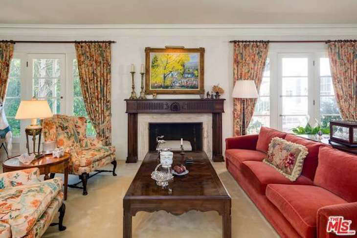 Matching florals extended from the armchairs to the curtains in the living room. The wooden mantel, preserved in the den, was one of the only original architectural details the team ultimately decided to replace.