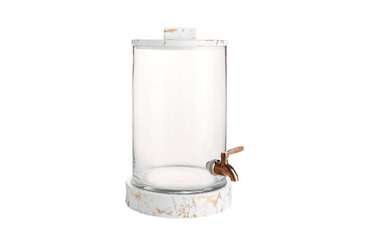 The Centro Marbleized Glass Beverage Dispenser sits on a white ceramic with bronze decal base and bronze-plated spigot; $69.97 at CB