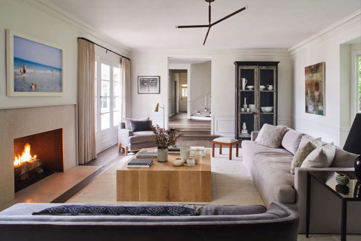 The living room was streamlined with a minimalist limestone mantel and wide-board fumed oak floors in place of wall-to-wall carpeting. The long sofa and wood coffee table are custom DISC designs. The vintage steel display cabinet came from Big Daddy&#8