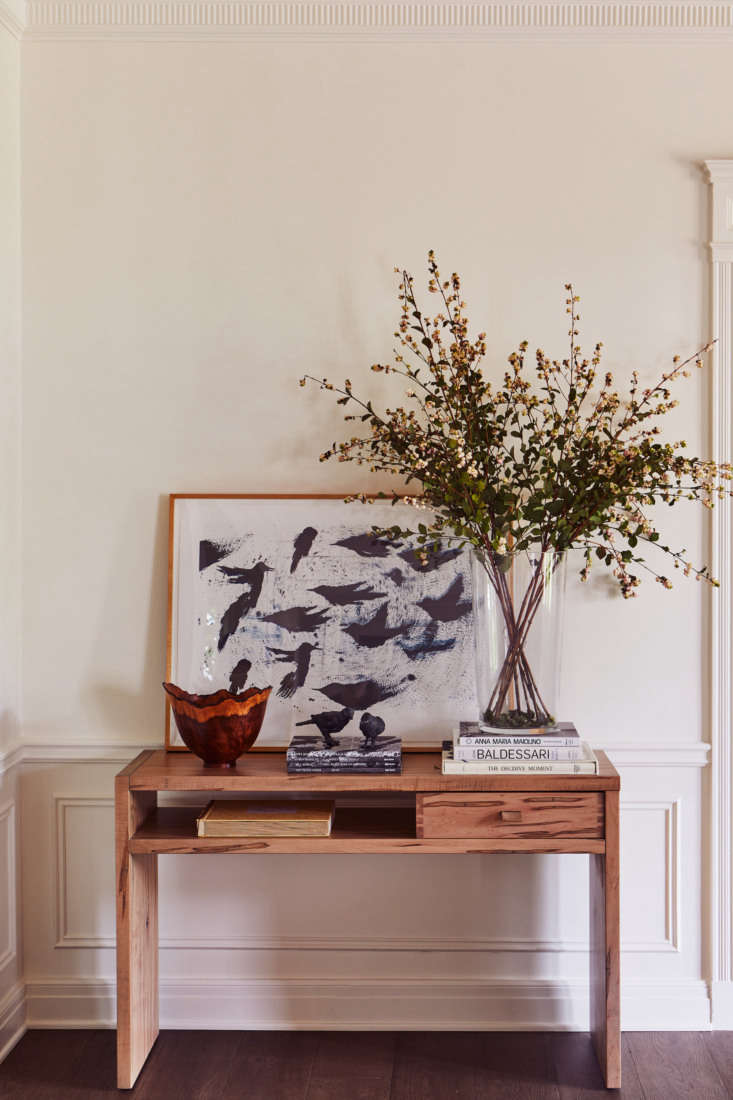 A custom console table displays a Ross Bleckner painting.