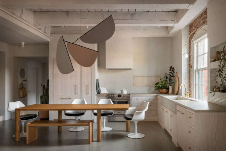 The kitchen, with the entryway just behind, has glimpses of the old—red brick, an arched window—among the new, including a custom concrete countertop and sink by Cement Elegance. A whimsicalmobile designed by GamFratesi hangs above the table.
