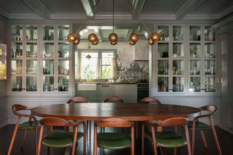 A wall of glass cabinets, which can be accessed from both sides, separates the kitchen from the dining room. The dining table is from BDDW, the Neva chairs are by Artisan, and the Trapeze ceiling light is by Apparatus.