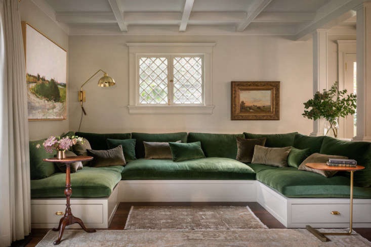 The family room is anchored by a built-in sofa, big enough to comfortably fit the clients and their two children, topped with plush cushions in a sumptuous green velvet.