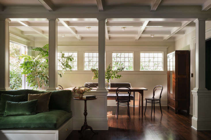 A casual breakfast room is just off the kitchen. The house had been stripped of its period details over the years; the design team made sure to add back in architectural interest, like coffered ceilings and columns. In the forefront is the family room.