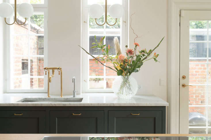 Set in a Carrara marble counter, the sink has a show-stopping brass mixer faucet from Danish brand Toni Amatur. The brass and opal glass globe ceiling fixtures are Michael Anastassiades&#8