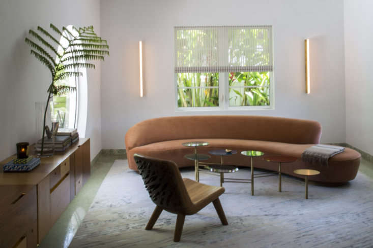 """Seen here in the Miami Beach home of Stephan Weishaupt is the original Vladimir Kagan Serpentine Sofa with Arm from 50 in coral velvet.""""I wanted an organic shape floating in the space,"""" says Weishaupt. """"I think it goes nicely with the round window."""" The sofa, model 0BSA, is still available to order through a Vladimir Kagan showroom; contact for pricing and more information."""