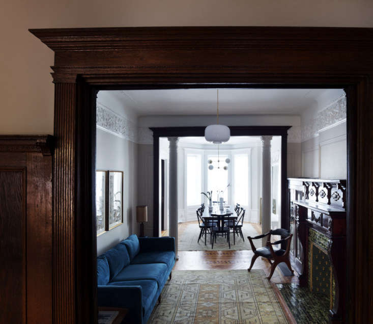 just off the dining room is a narrow parlor, fitted with a blue velvet couch ac 14
