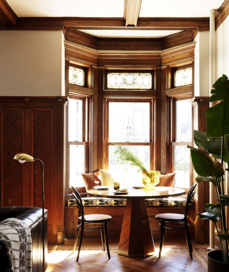 caned chairs flank a breakfast table, set into a bow window. the stained glass  16