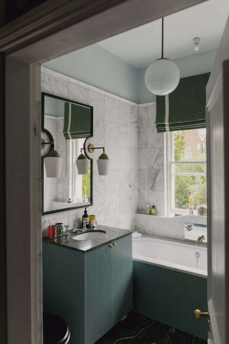 Semicircle cutouts in the bathroom mirror accommodate sconces.