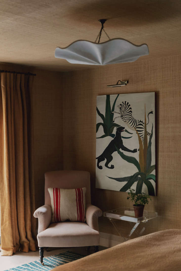 In the guest room, sea-grass wallpaper covers both the walls and the ceiling.