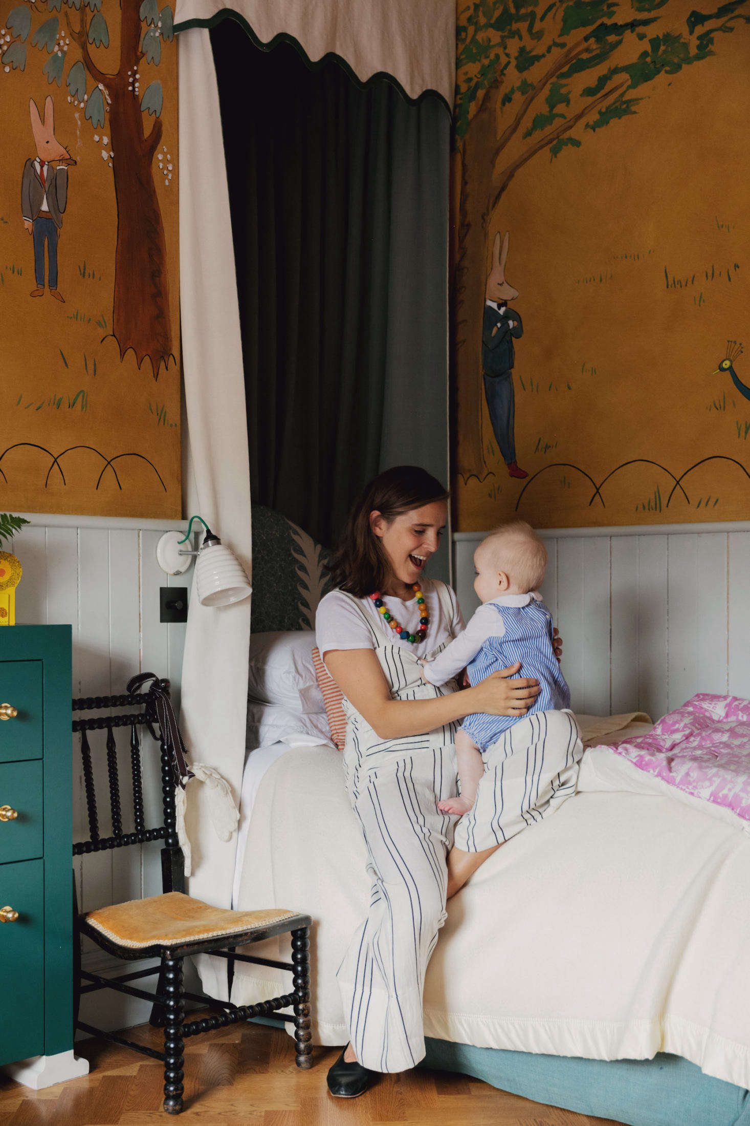 Heuman with her baby in the whimsical bedroom of her older daughter, a toddler.