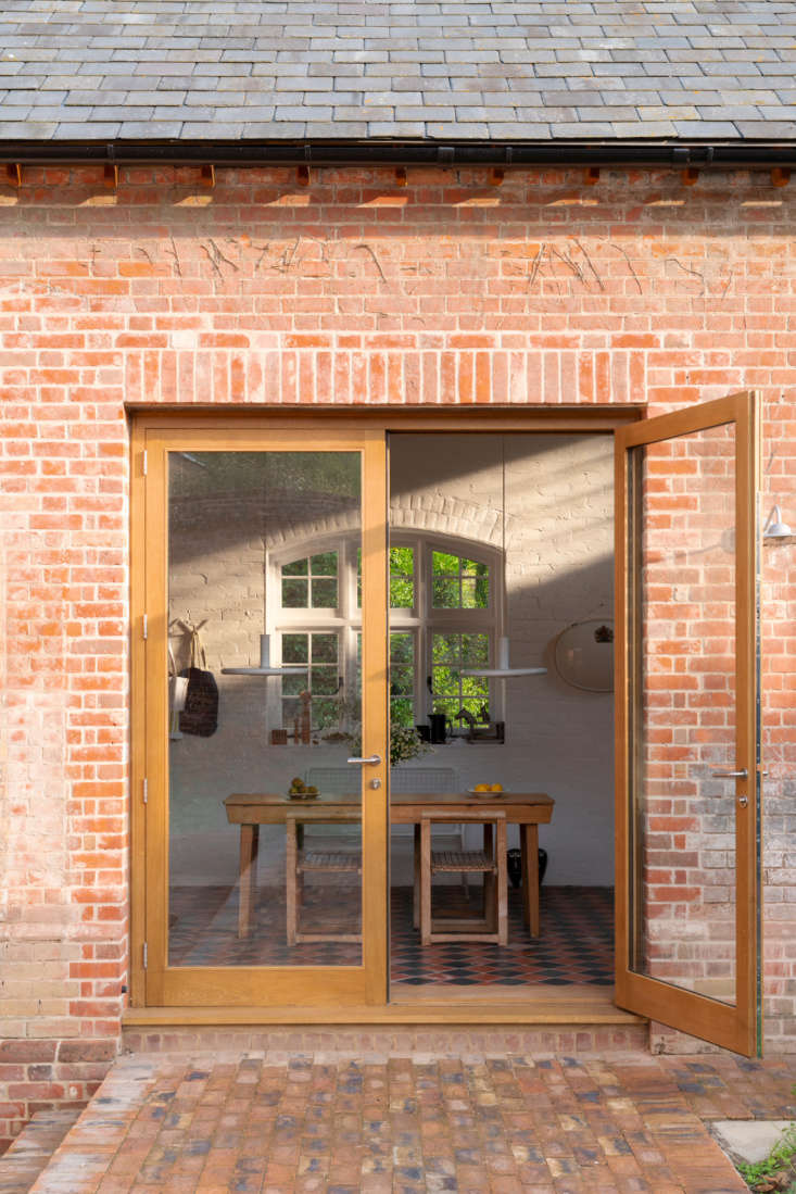 Glazed double doors framed in oak open to a brick terrace and walled garden. The grocer who once used the building as a storeroom planted tomatoes that Sandy says &#8