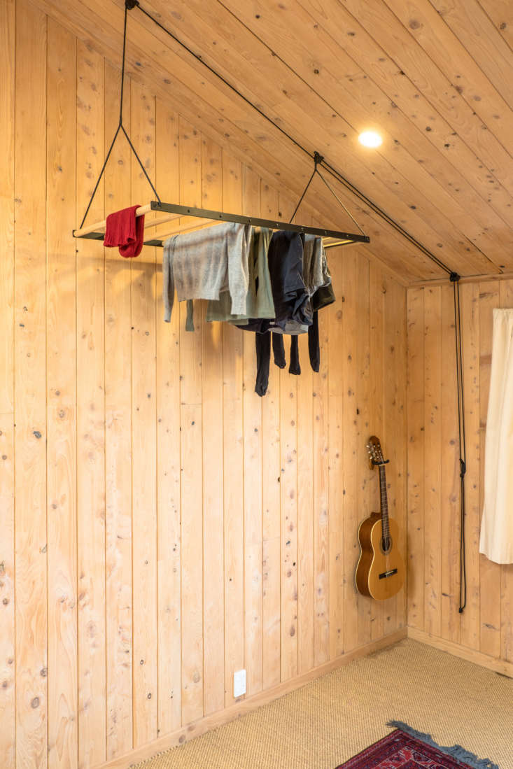 A George & Willy pulley system drying rack hangs in a corner of the primary bedroom where it takes up little space and allows clothes to dry in the warmest air. Read about the design in Object of Desire: A Hanging Laundry Rack.