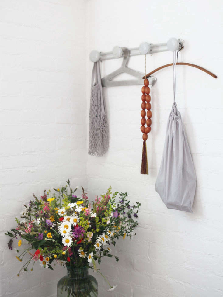 A pair of vintage French metal hanging rack flank the bed in the brick-walled mezzanine.
