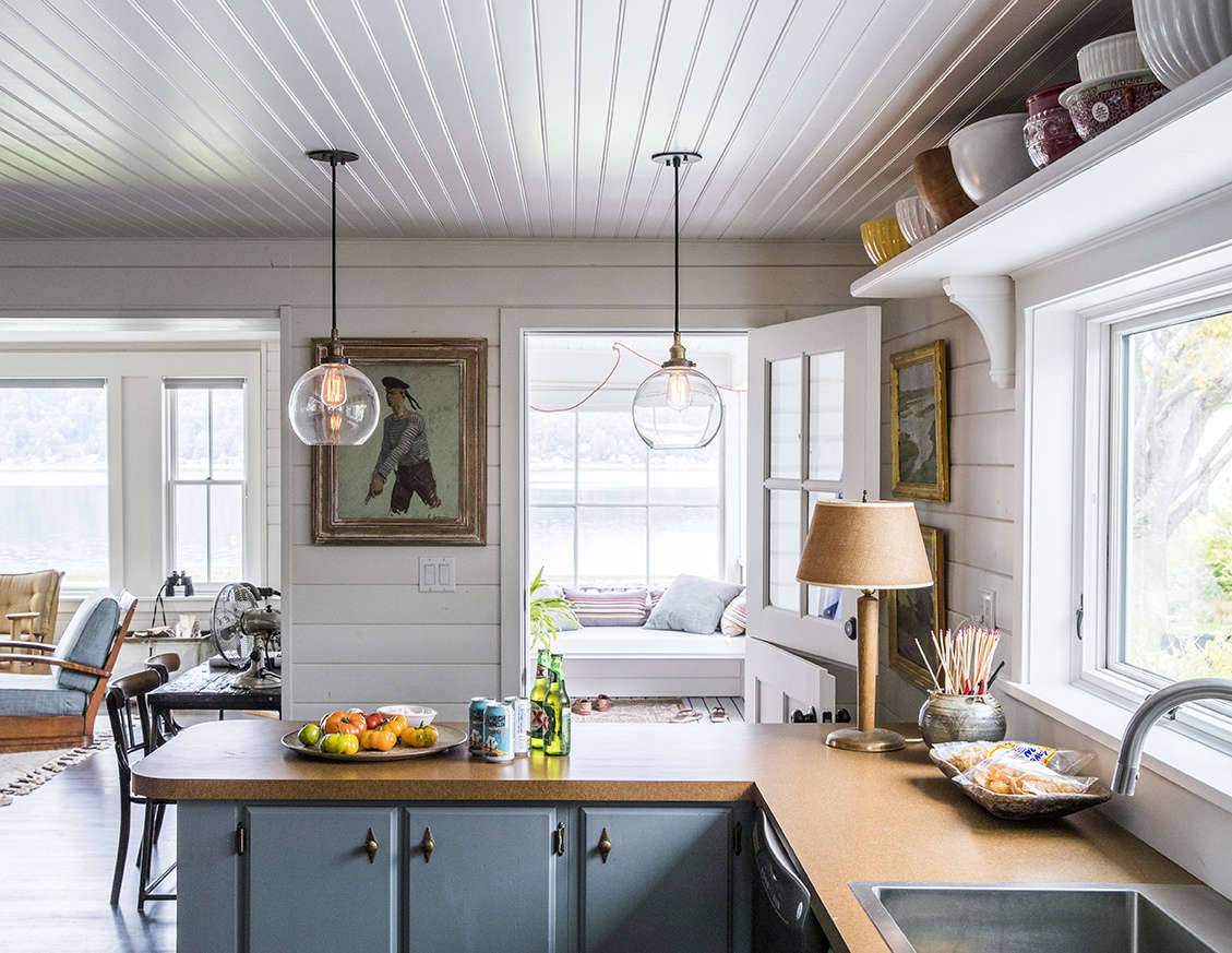 The only element that survived the renovation? The 50s kitchen cabinets, now painted a gray-blue and appointed with brass hardware for a nautical feel. Formica countertops (new) further the old beach-cottage story.