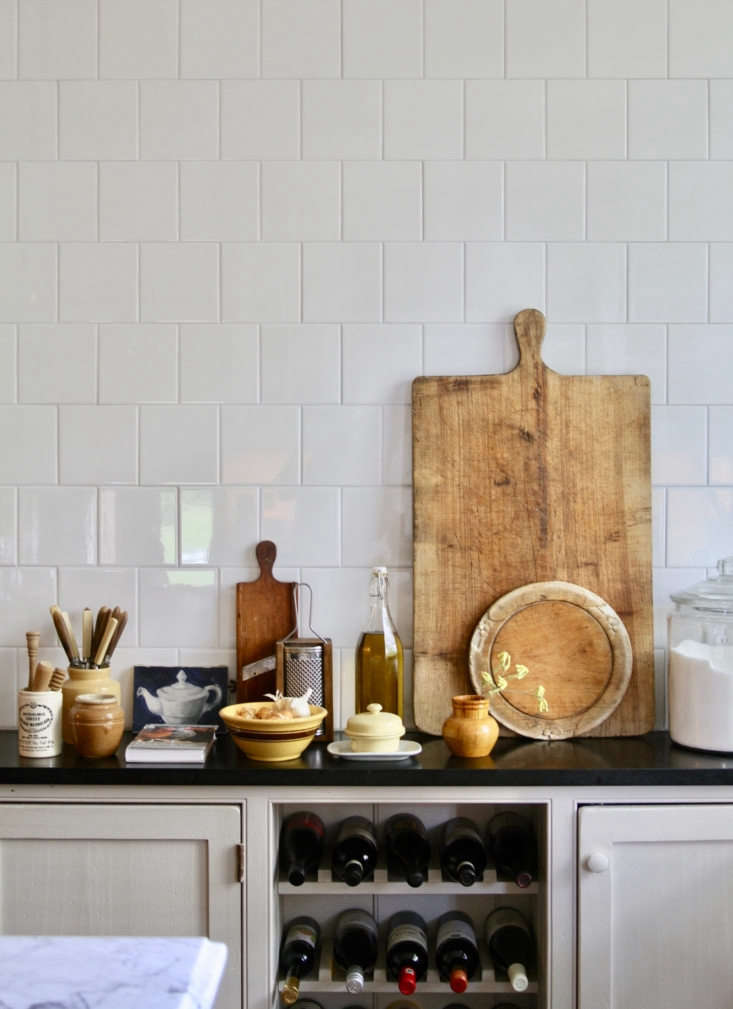Simple square white tiles in the kitchen. The couple are geniuses at layering textures, spotlighting patina, and finding beauty in the mundane.