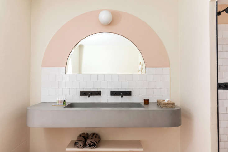 The painted arches are a clever way to introduce color without fully going to town. The sinks are made of local stone finished with a thin layer of concrete. French enameled tiles serve as a backsplash.