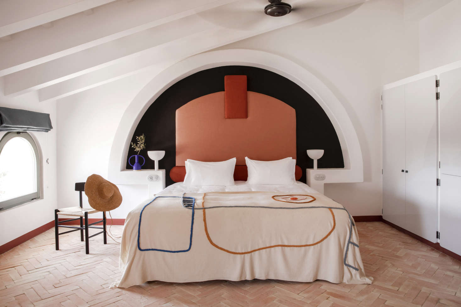 Meilichzon is known for her inventive beds—and never repeats herself. At Menorca Experimental, she built altar-like concrete alcoves finished in white lime and inset with upholstered headrests in two shades of terra-cotta. The embroidered cotton bedspreads were made for the hotel by textile and ceramic studioLRNCE of Morocco. The herringbone floor is composed of terra-cotta.