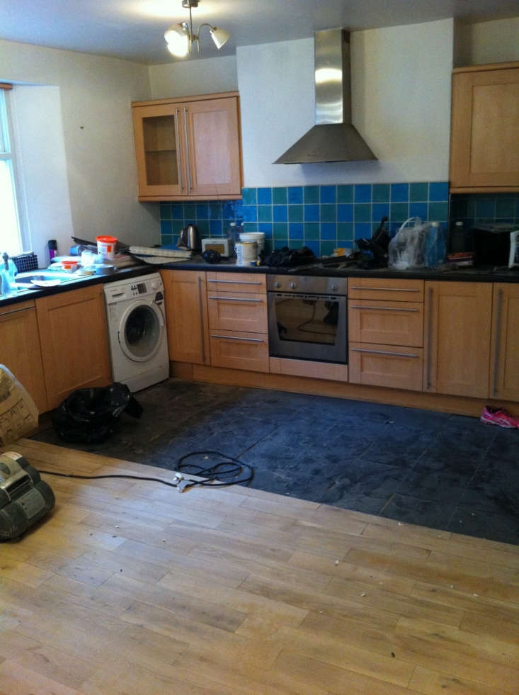 The former kitchen with dated cabinets and inelegant flooring.