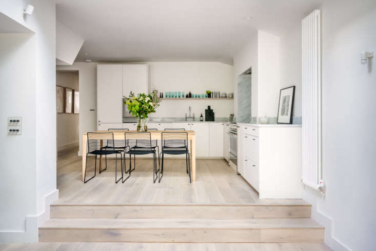 The open kitchen is in the addition. Stackable chairs from Hay surround a handcrafted table by Ethnicraft. Note the stylish light switches (at left): &#8