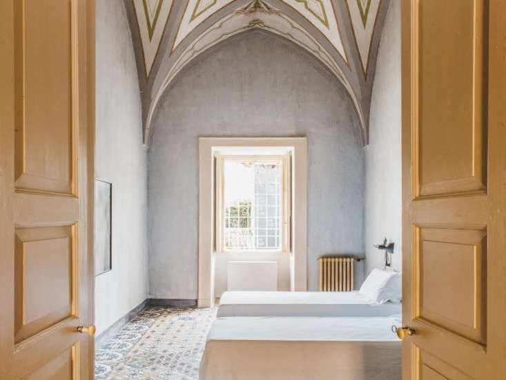 Another guest bedroom is left almost completely undressed so that the bones—a dramatic vaulted ceilings and double doors painted entirely in yellow—are the focus.