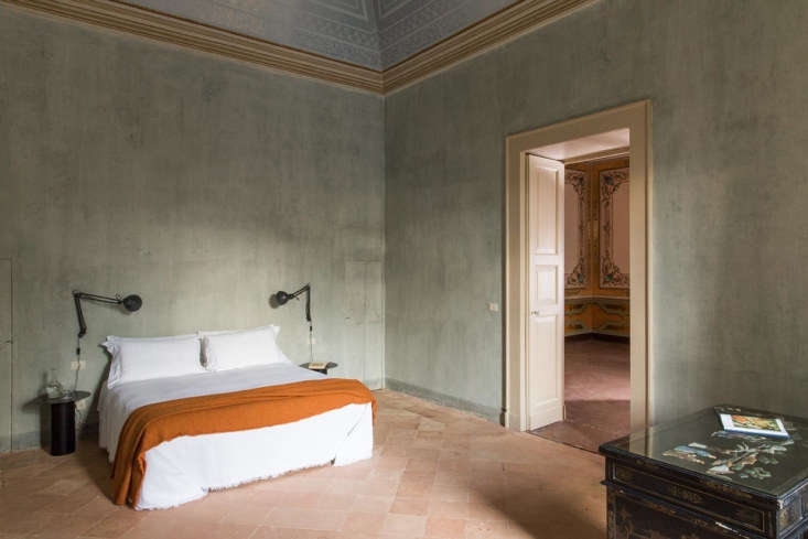 A suite bedroom in hues of pale blue and persimmon.