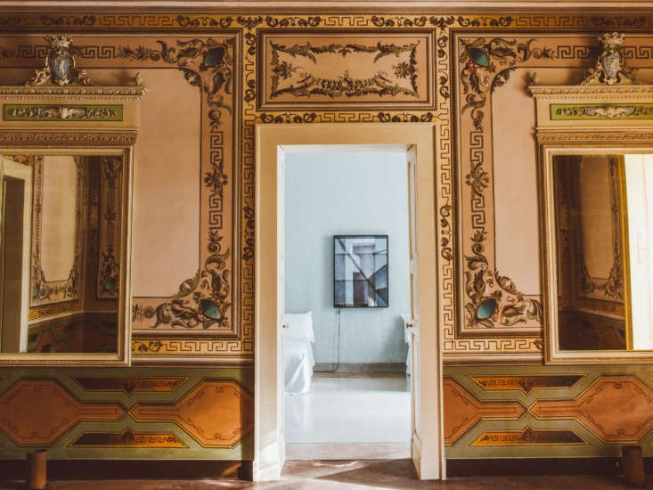 A particularly ornate hallway, with gold-hued frescoes and mirrors, leads to one of the suite&#8