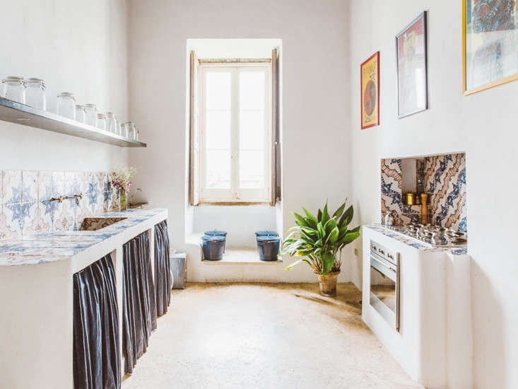 The Suite Apartment features a simple kitchen, with tiled countertops and backsplash and skirted storage.