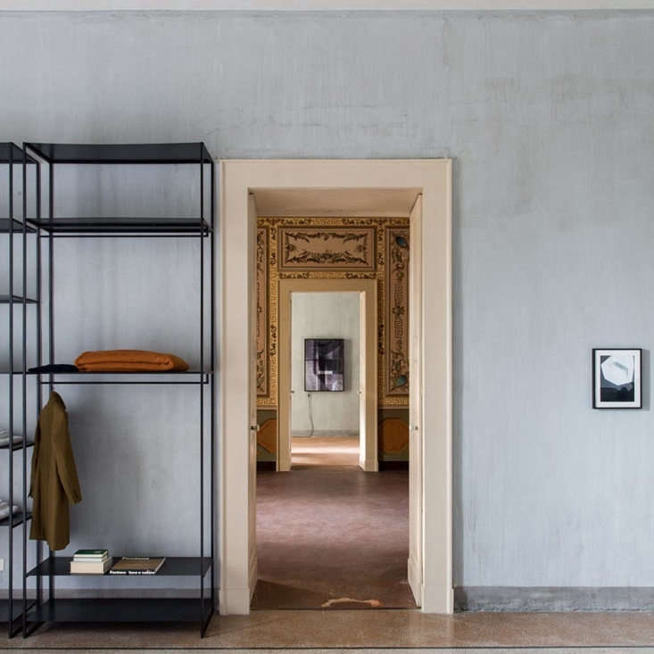 In another suite, original textured walls, left bare, mixes with a clean-lined open wardrobe.