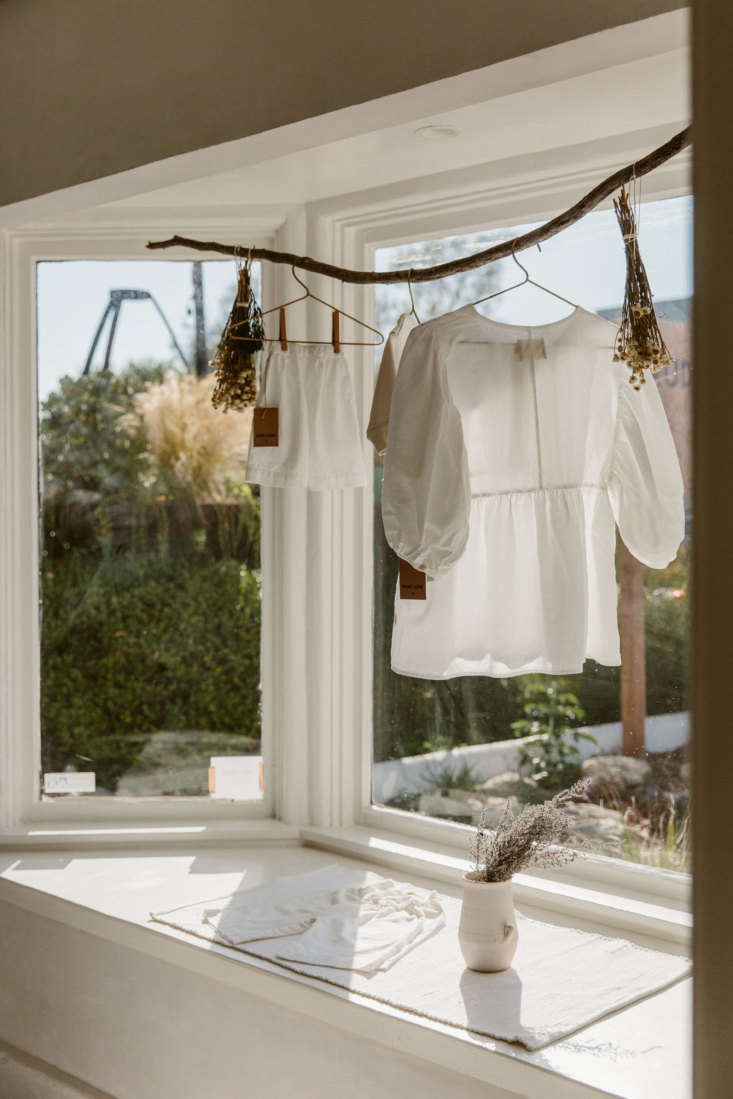 In the front window, a curved branch displays a Rudy Jude Day Blouse—and bundles of dried flowers. (For more ideas like this, seeThe New Rusticity: loading=
