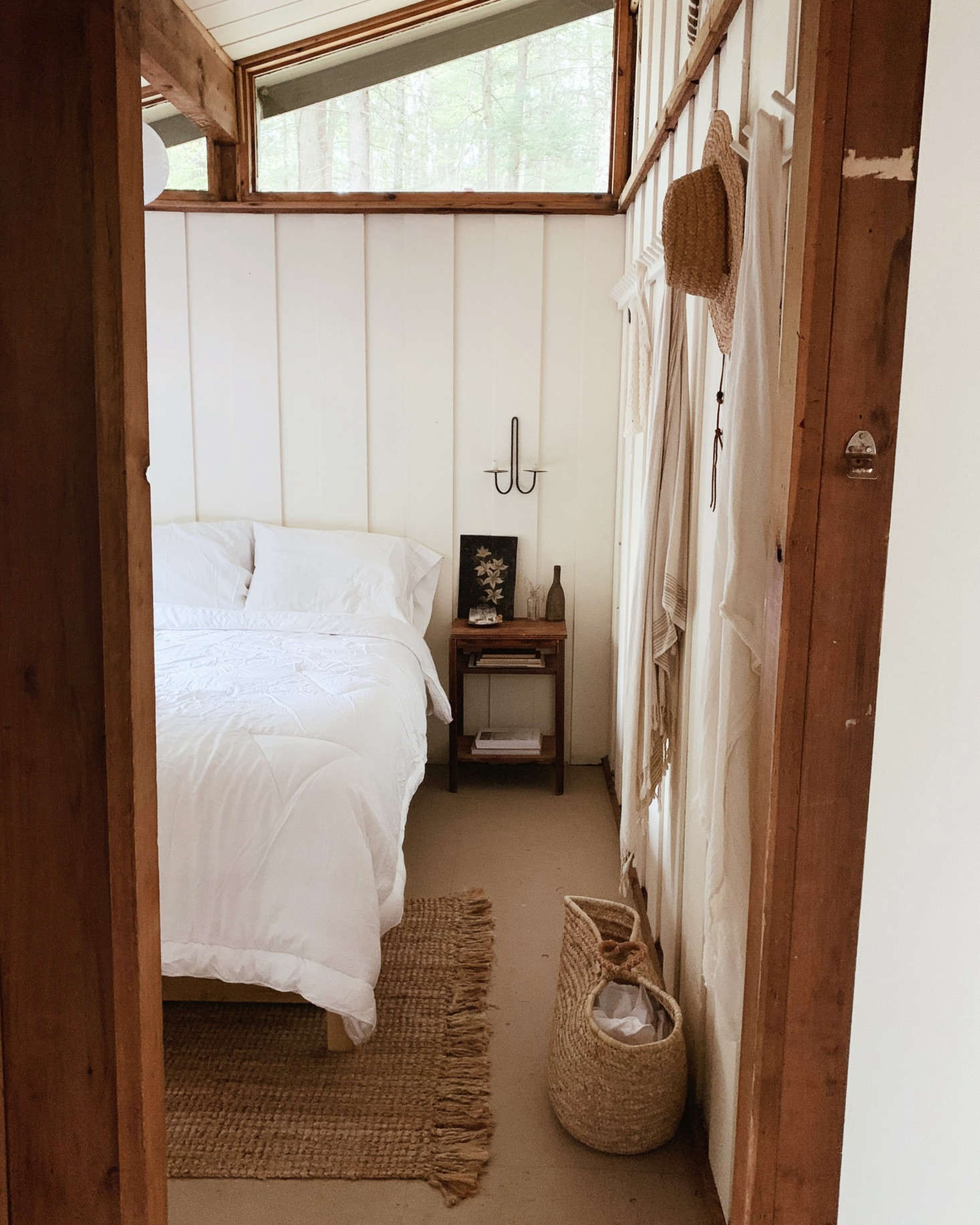 Into the bedroom, which is kept bright and spacious with white walls and linens.