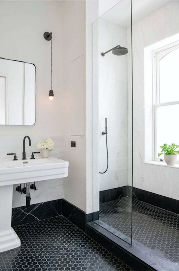 Hexagon tiles, a classic NYC bathroom flooring, looks modern in black. The room is paneled in white Rhino marble with Nero Marquina marble wainscoting.