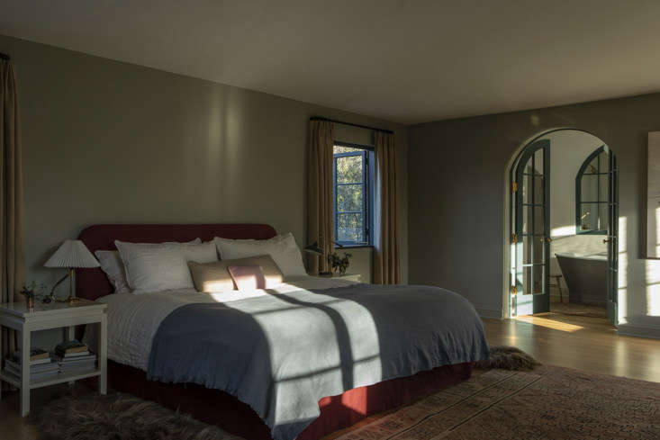 The master bedroom is cloaked in rich jewel tones and sunlight.