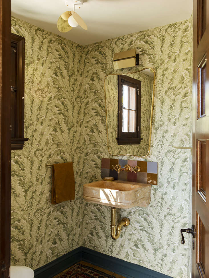 The powder room off the entry is patterned with Florencecourt, a wallpaper from the archives of Cole & Son of England. A Gio Ponti Wall Mirror hangs over a th-century Italian limestone basin. The brass ceiling fixture is from Atelier Areti and the sconce is by LA designer Brendan Ravenhill&#8
