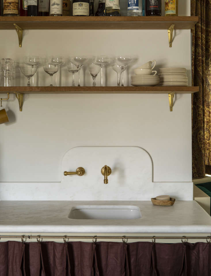 Three favorite details: the curved backsplash of Namibia White marble (with one-handle brass faucet by Watermark), bullnose-edge counter, and bar skirt of pleated plum handkerchief linen from Gray Line Linen of NYC, a notable affordable fabric source.