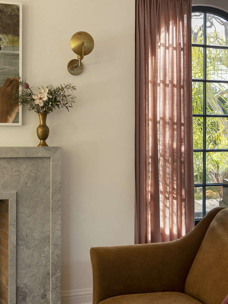 LA Autumnal A 1920s House Makeover Composed in Jewel Tones The room&#8\2\17;s simple marble mantel replaced a heavy wood design. Gone, too, are the room&#8\2\17;s scrolling wrought iron wall lights: the brass Orbit Sconces are by Workstead and came out of the family&#8\2\17;s former house.