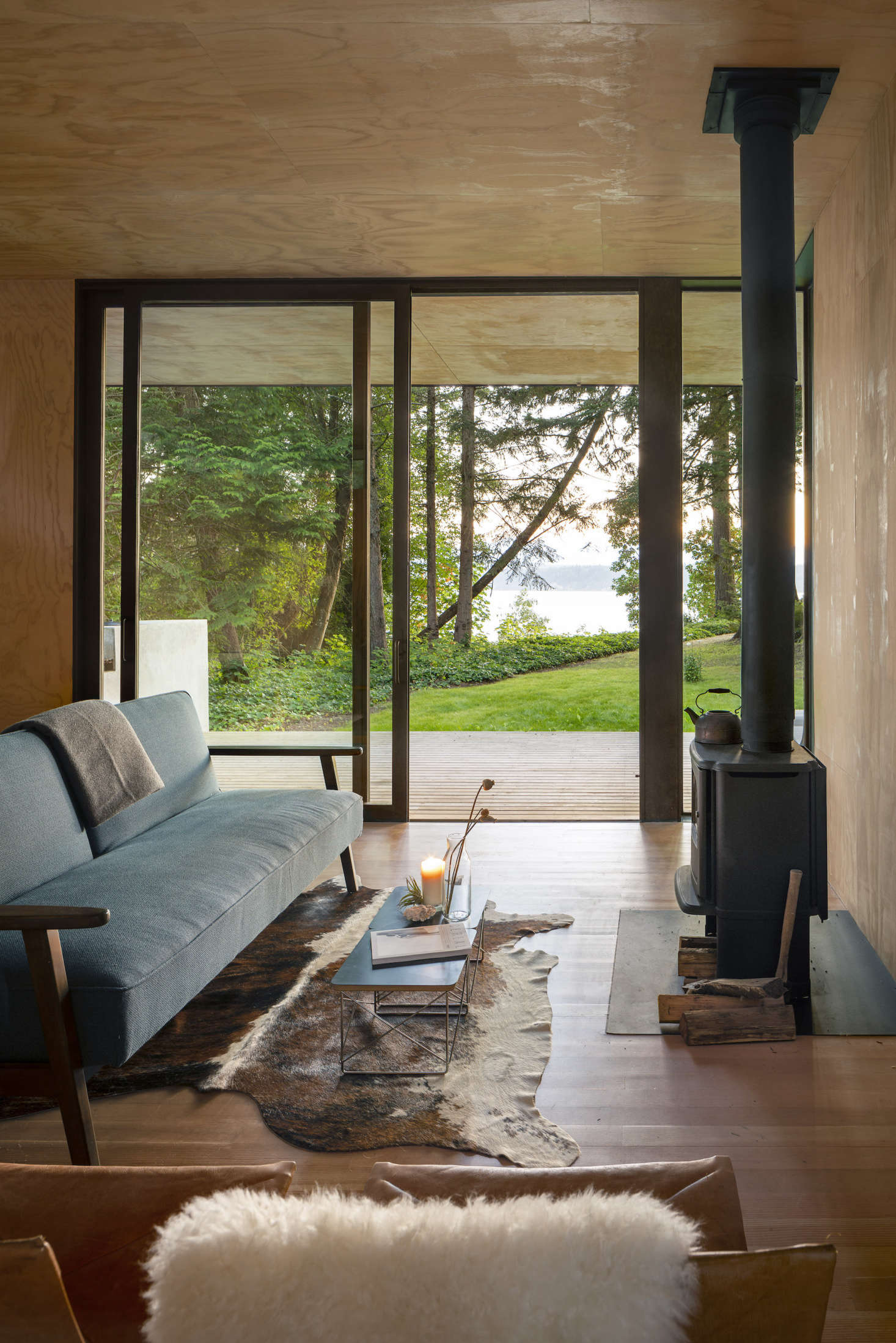 Mid-century furniture throughout reinforces simple, clean lines. The wood-burning stove is from Danish company Morsø; model 3440 is designed to be environmentally friendly. Ten-foot-high glass doors by Lindal ensure unimpeded views of the canal.