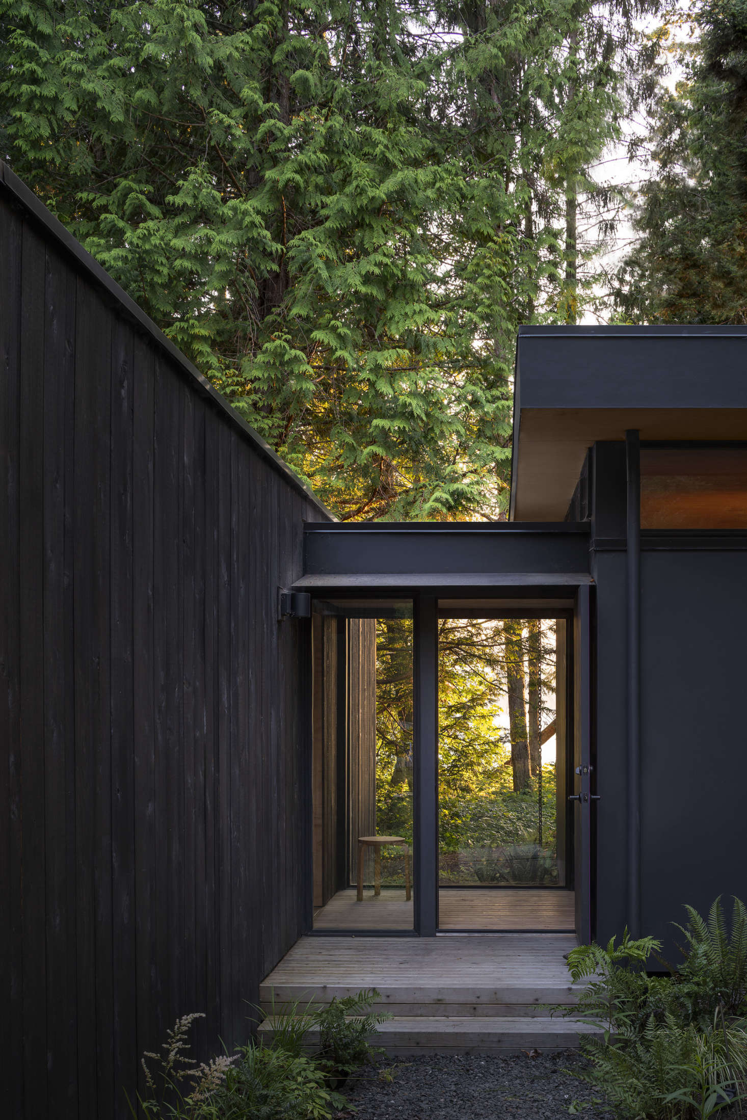 A glass vestibule connects the original main cabin to the new addition, which now houses a bedroom and bathroom. The rough-sawn cedar siding is unpainted to encourage natural aging.
