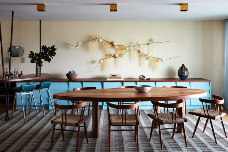 Adjacent to the kitchen is the dining area, with a Commune-designed console with attached bar. Surrounding the table are George Nakashima&#8