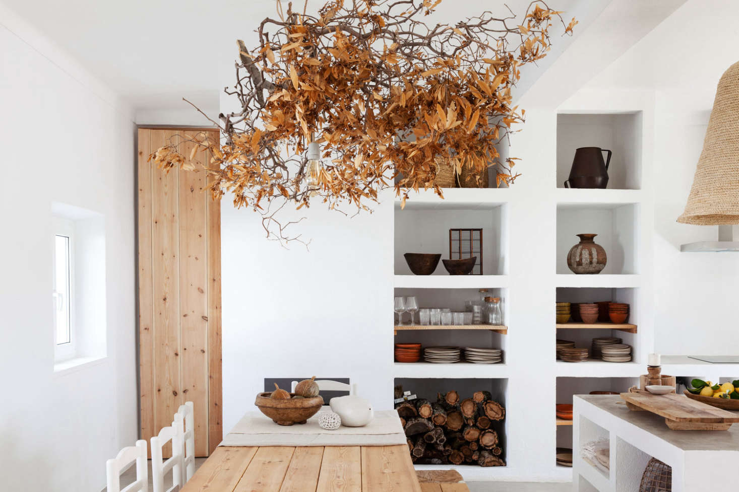 The guest house kitchen, with sculptural white shelves, a wood-plank table, and a tangle of dried leaves hung above. (For a similar autumnal look, see Bringing in the Sheaves: Harvest Table Inspiration from Caro of Somerset.)