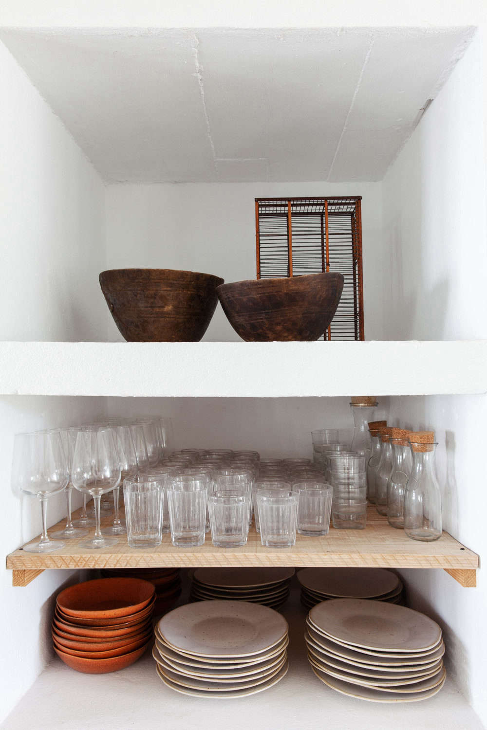 Shelves hold stacks of cream and terra cotta-colored dinnerware.