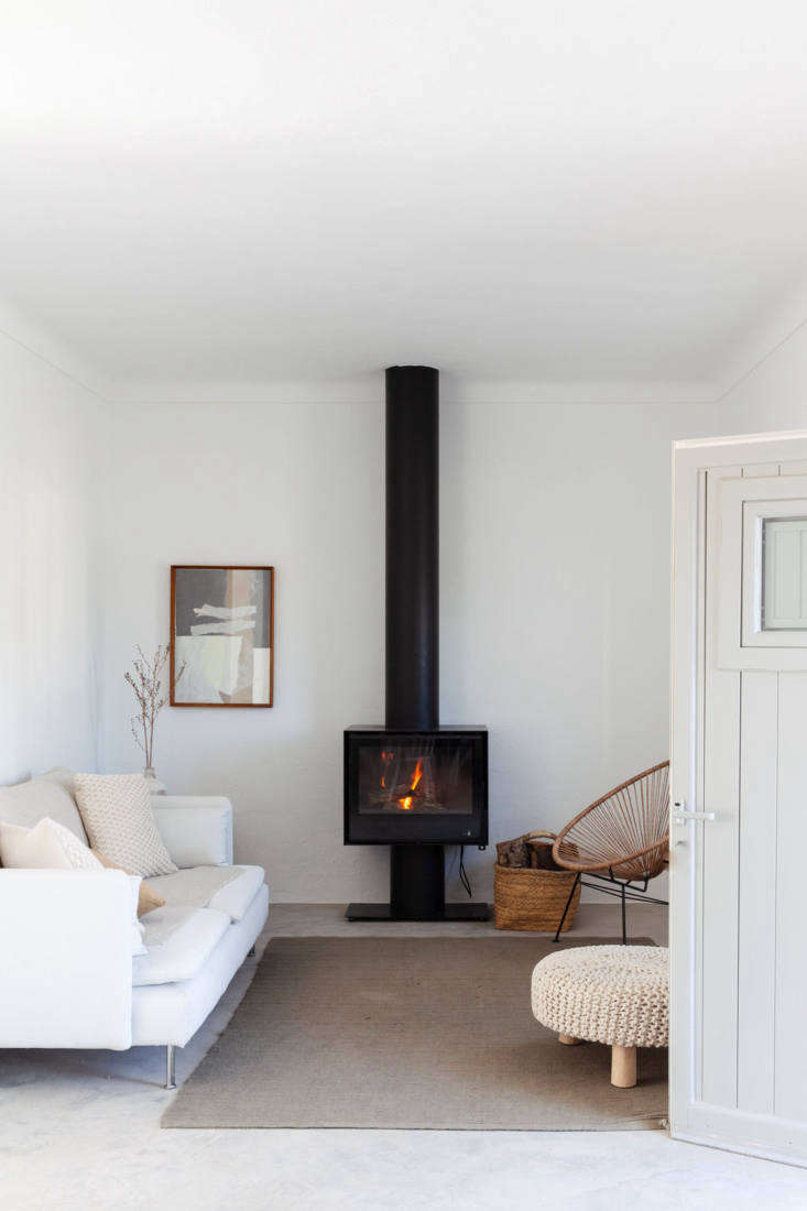A wood stove anchors—and warms—a living area; a basket keeps logs close by.