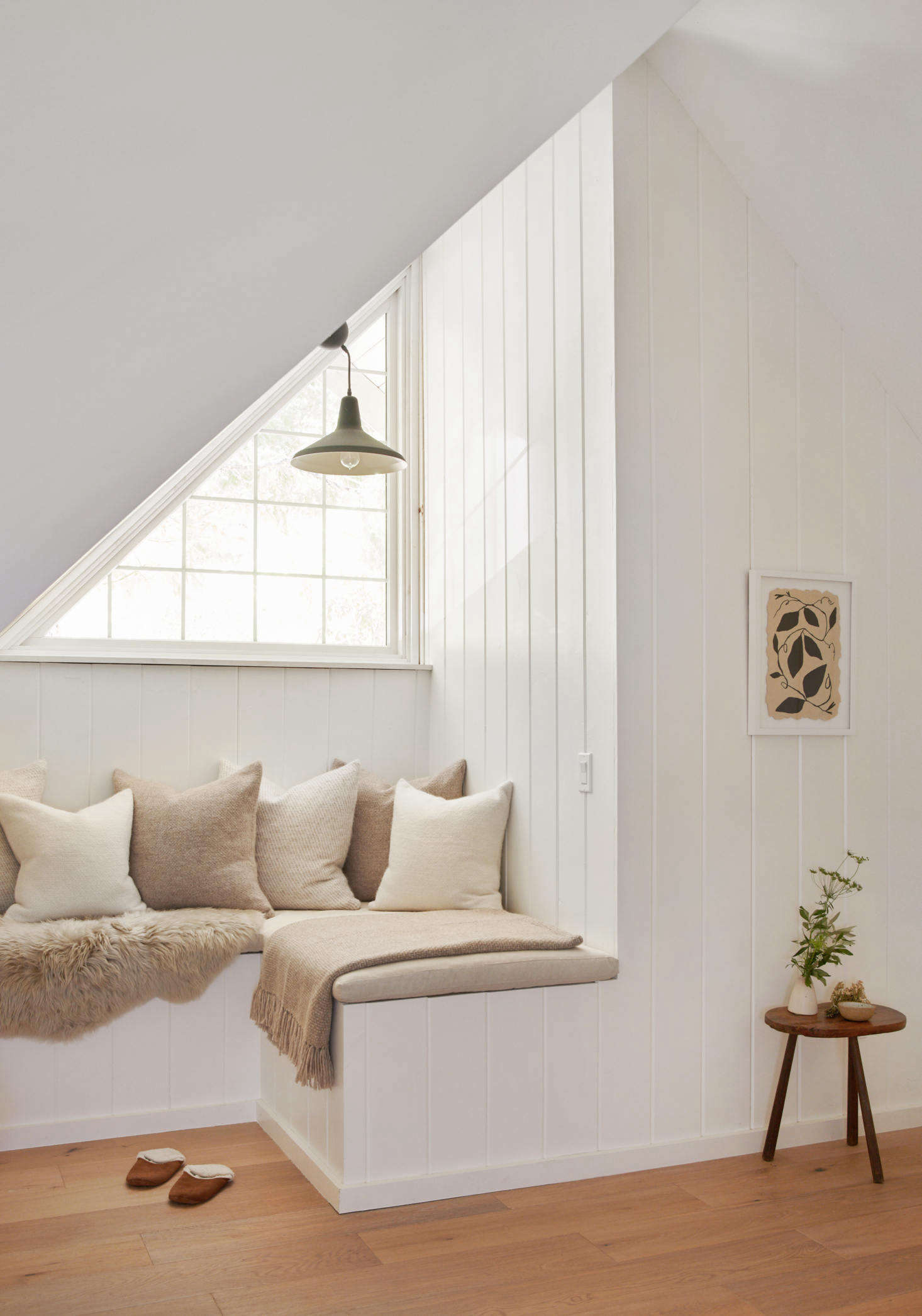 A built-in sitting area makes use of a nook beneath a window.