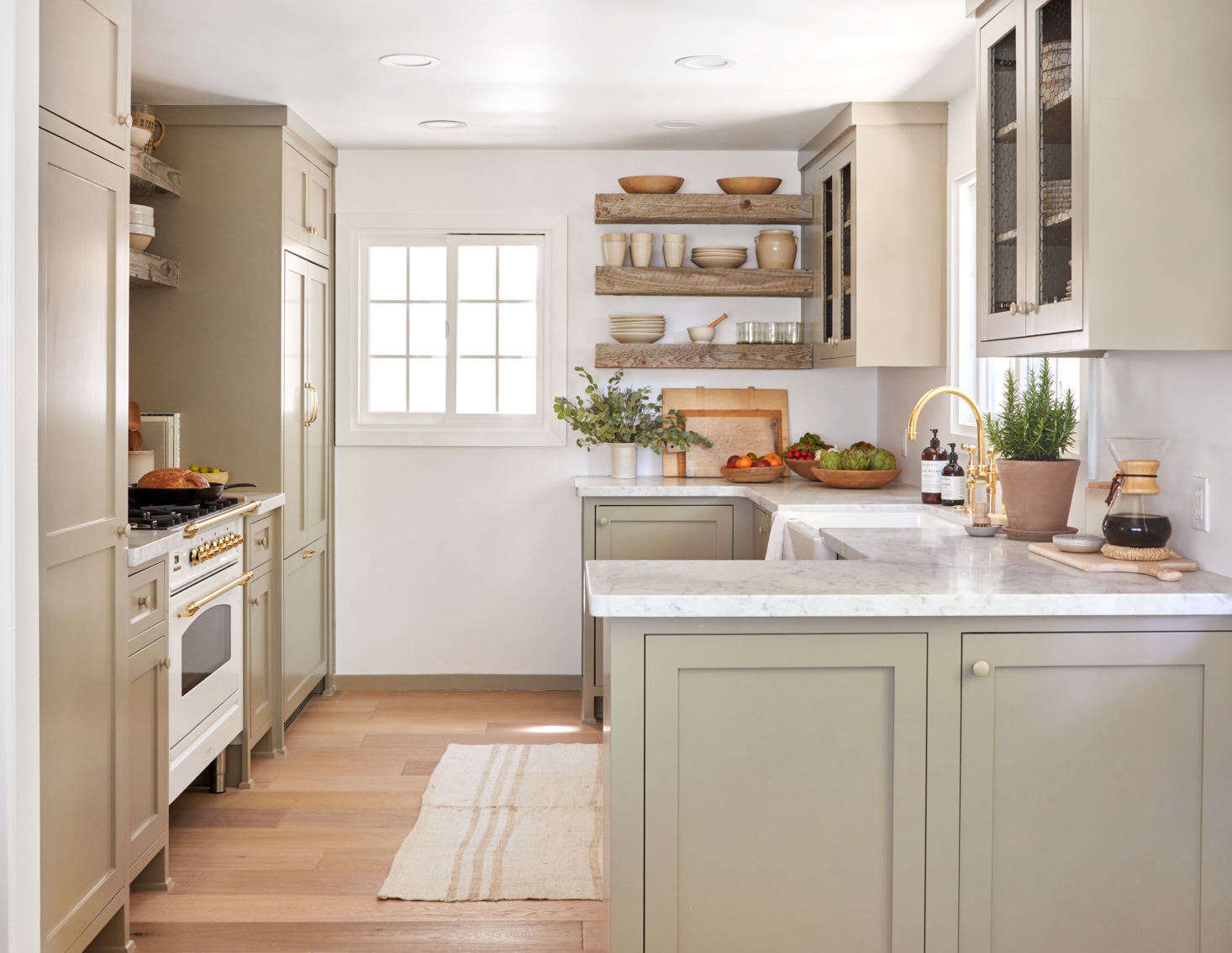 The team re-envisioned a dark and cramped kitchen into a compact but open-feeling space. The cabinets are custom, made by a local carpenter and painted in a subtle earthy tone, Farrow & Ball&#8