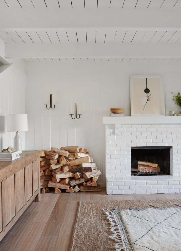 The original fireplace, painted white, is paired with layered rugs and a generous stack of firewood. The wall-mounted candle holders are from June Home Supply. (They&#8